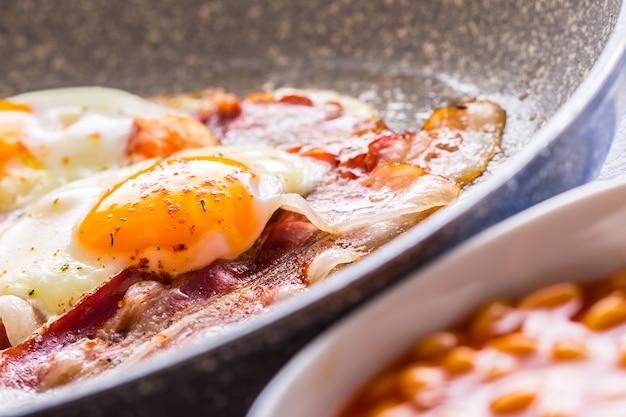 Яйца и ветчина жарение яиц и бекона на керамической сковороде английский завтрак