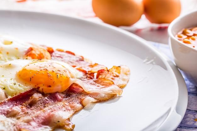 Ветчина и яйца. бекон и яйца. яйцо посолить и посыпать красным перцем. английский завтрак.