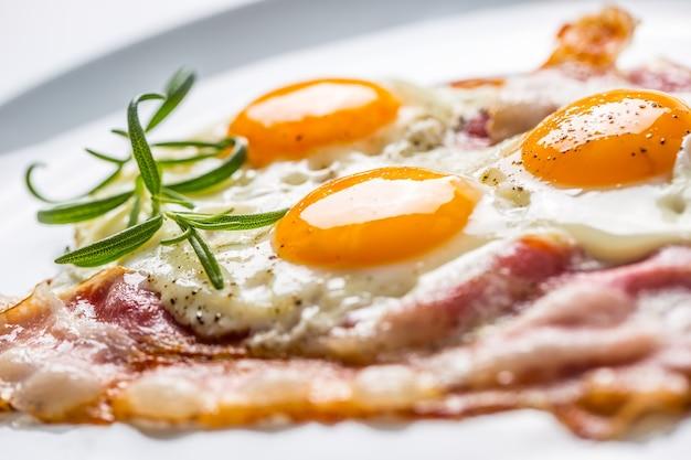 햄과 계란. 베이컨과 달걀. 하얀 접시에 후추와 소금에 절인 계란입니다. 영국식 아침 식사.
