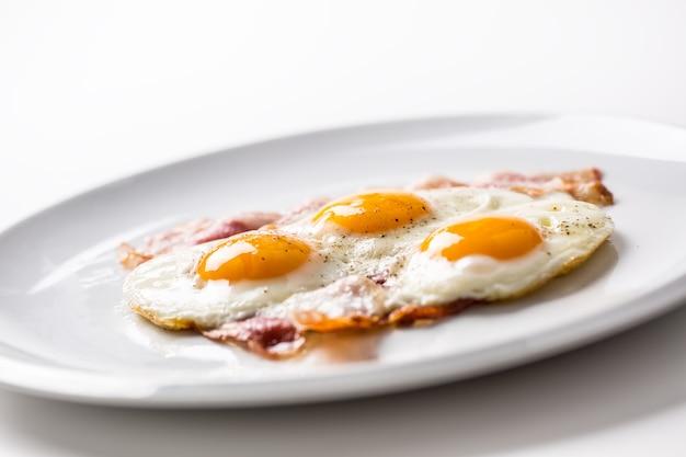 Ветчина и яйца. бекон и яйца. соленое яйцо с перцем на белой тарелке. английский завтрак.