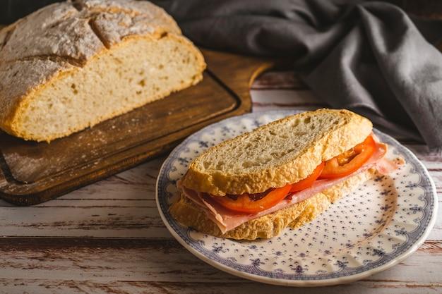 소박하고 전원적인 분위기에서 수제 빵 조각으로 준비한 햄과 토마토 샌드위치. 풍경보기.