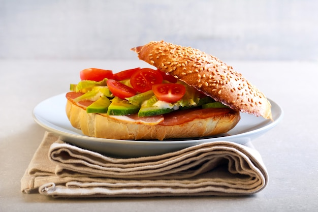 Ham, avocado, tomato and lettuce bagel on plate