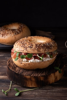 Ham bagel for breakfast on a dark wooden background, sandwich with ricotta, prosciutto and microgreens, rustic style.