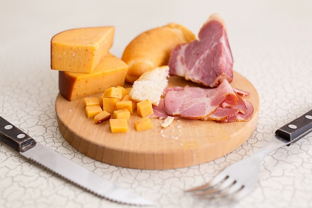Ham, cheese and bread on a wooden cutting board