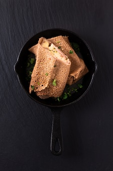 Ham and cheese crepe in iron skillet cast on black slate background