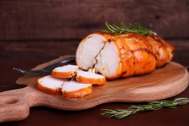 Ham chicken breast baked with rosemary on a wooden cutting board