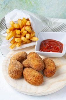 Ham and chicken croquettes with chips and fried tomato