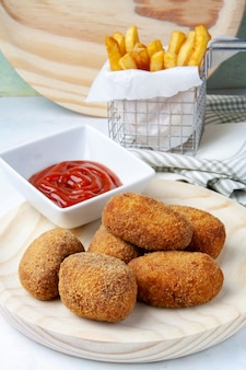 Ham and chicken croquettes with chips and tomato