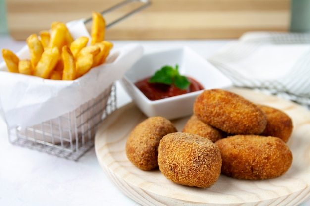 Ham and chicken croquettes with fried tomate and chips