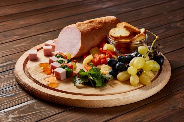 Ветчина, украшенная овощами, фруктами и зеленью с соусами и хлебом на деревянной тарелке на темном деревянном столе.