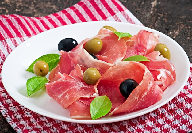 Ham, olives, basil on old wooden