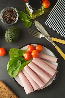 Ham rolled on plate with fresh vegetables dark background