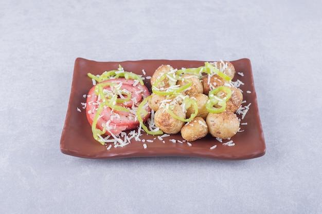 Involtini di prosciutto e patate fritte sul piatto scuro.