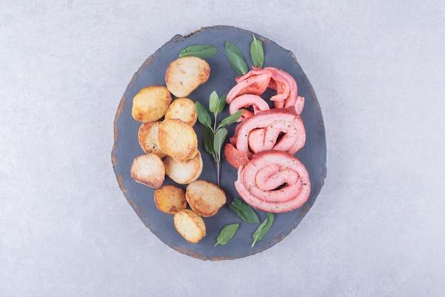 Involtini di prosciutto e patate fritte su pezzo di legno.