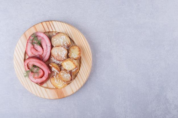 Involtini di prosciutto e patate fritte sul piatto di legno.