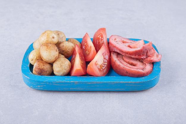 블루 접시에 햄 롤, 토마토, 튀긴 된 감자.