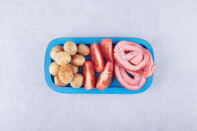 青いプレートにハムロール、トマト、フライドポテト。