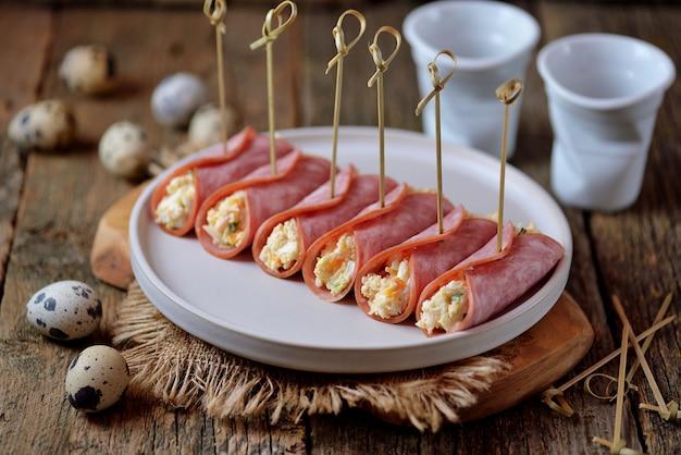 Рулетики из ветчины с мягким сыром, вареными яйцами и зеленым луком.
