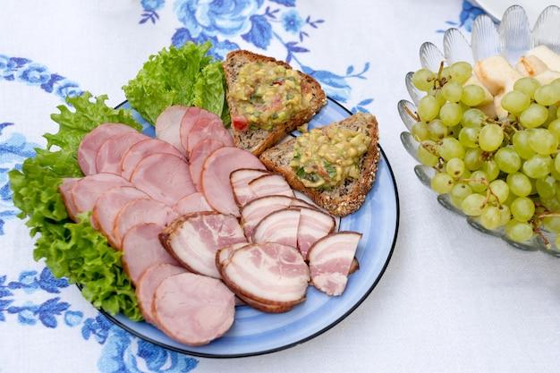 Ветчина, бутерброды с домашним гуакамоле и тарелка винограда на деревенском столе в саду.