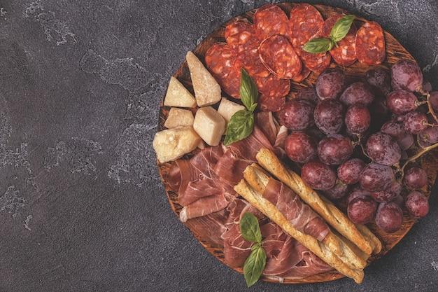 暗いテーブルにハム、ソーセージ、ブドウ、チーズ
