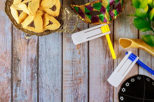 ハマンス耳クッキーノイズメーカーとプリムのお祝いユダヤ人のカーニバルの休日のためのマスク