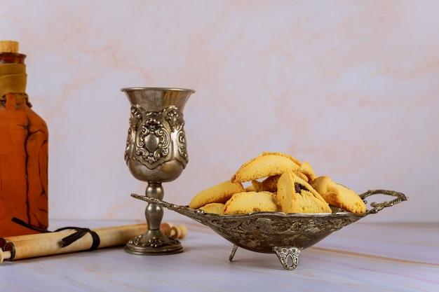 プリムスのお祝いのユダヤ人の休日カーニバルコーシャワインのhamans耳クッキー