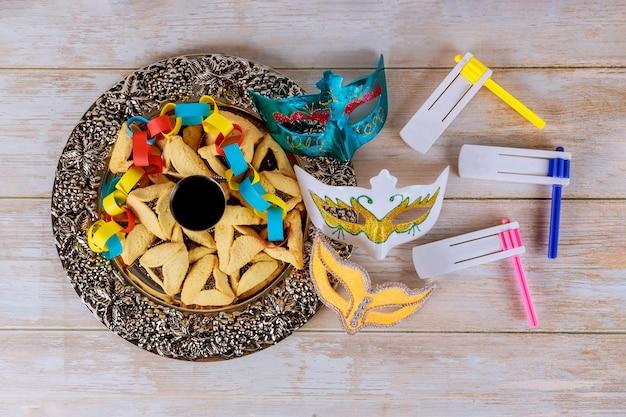 プリム祭のユダヤ人のカーニバルの休日のためのhamans耳クッキーノイズメーカーとマスク