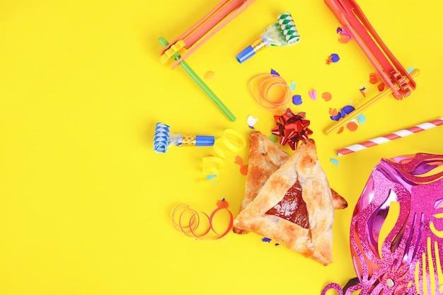 Пурим фон с карнавальной маской, праздничный костюм и hamantaschen печенье.