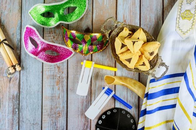 Празднование еврейского карнавала пурим с печеньем hamantaschen, шумоглушителем и маской с пергаментом