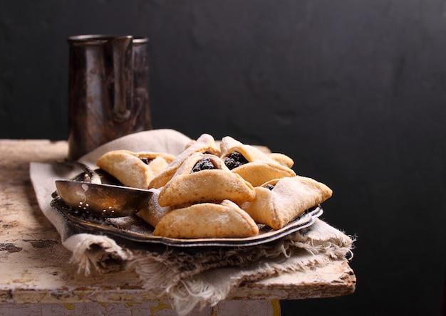 ケシの実とライシン、皿の上の砂糖のアイシングが付いているhamantaschenクッキーは、プリムのユダヤ人の祭りのために調理されました。