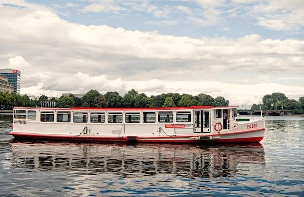 ドイツ、ハンブルク-2017年9月7日:船舶、輸送、輸送。夏休み、放浪癖。クルーザーボートは曇り空の川の水に浮かんでいます。ウォーターツアー、旅行アドベンチャーボートでの旅行