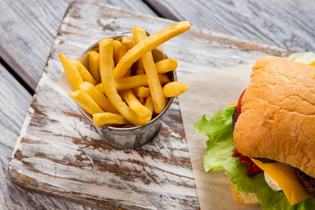 감자 튀김과 햄버거와 양동이입니다. 감자 튀김의 상위 뷰입니다. 식당에서 맛있는 식사. 너무 신선하고 바삭합니다.