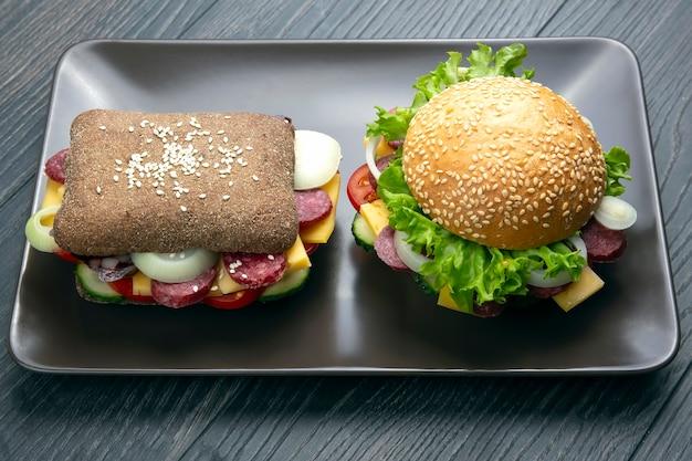 ハンバーガーと野菜とソーセージのサンドイッチ。