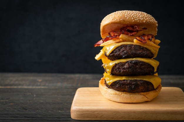 Hamburger or beef burgers with cheese, bacon and french fries - unhealthy food style