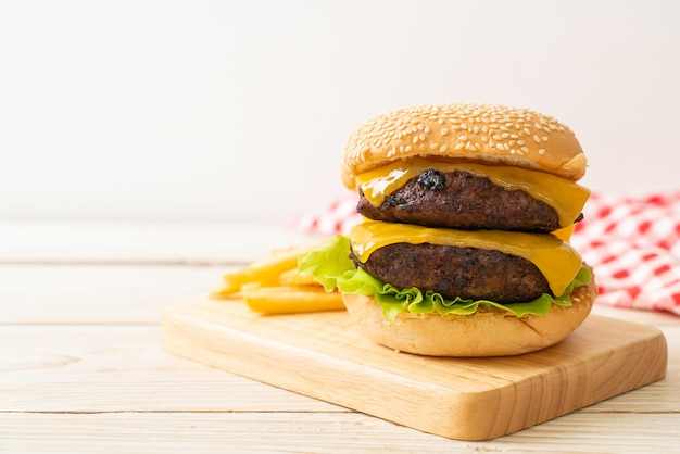 Hamburger or beef burgers with cheese and french fries - unhealthy food style