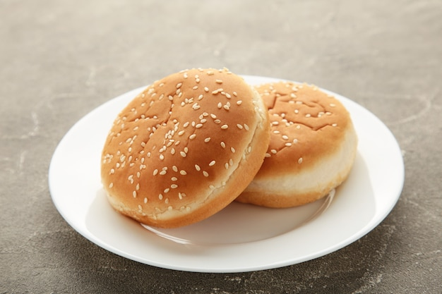 Hamburger buns in plate on grey background. top view