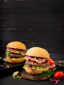 Hamburger burger with beef, tomato, pickled cucumber and fried bacon