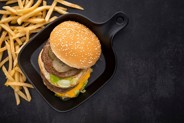 Hamburger, cheeseburger with double cutlet in black pan and french fries, top view