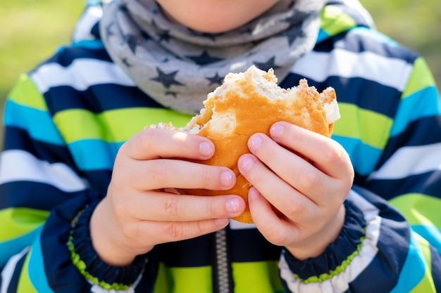 子供の手のハンバーガーのクローズアップ。散歩のおやつ