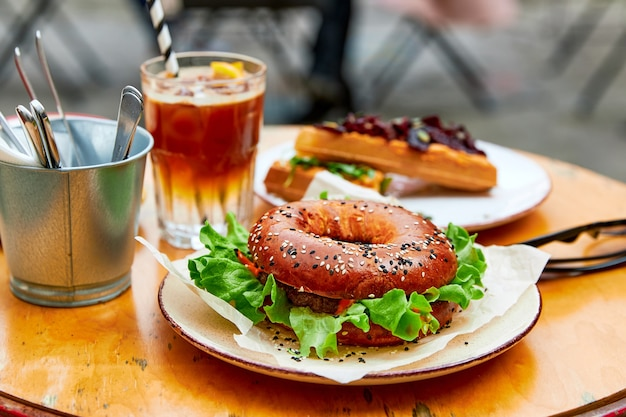 Hamburger in the form of a dout sandwiches coffee lots of food on a wooden table