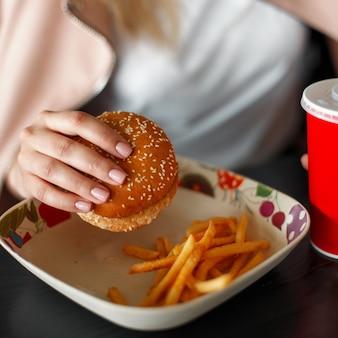 Hamburger, french fries and cola. woman eats fast food. close-up