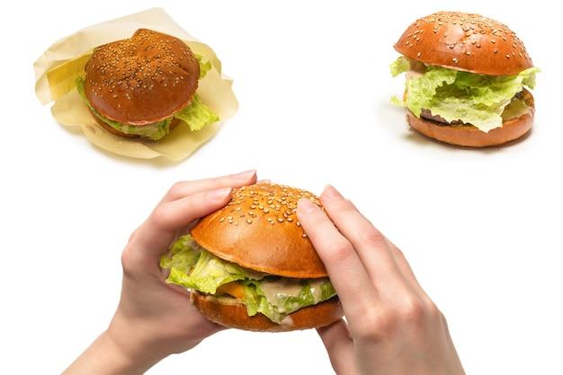 白い背景で隔離の女性の手のハンバーガー。上面図。