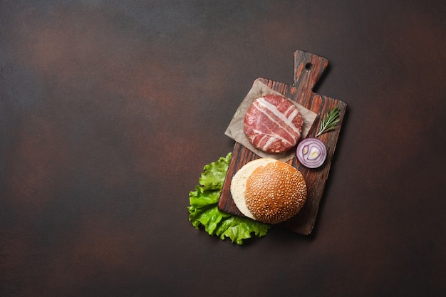 Hamburger ingredients raw cutlet, lettuce, bun, cucumbers and onion on rusty background. top view with place for your text.