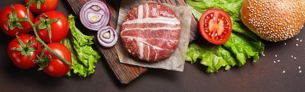 さびた背景にハンバーガーの材料の生のカツレツ、トマト、レタス、パン、チーズ、きゅうり、玉ねぎ。テキストの場所を含む上面図。