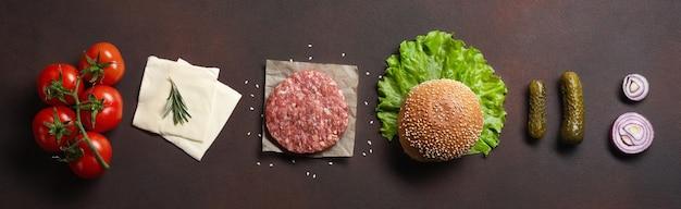 さびた背景にハンバーガーの材料の生のカツレツ、トマト、レタス、パン、チーズ、きゅうり、玉ねぎ。上面図
