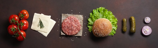 Hamburger ingredients raw cutlet, tomatos, lettuce, bun, cheese, cucumbers and onion on rusty background. top view
