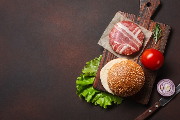 Hamburger ingredients raw cutlet, tomatos, lettuce, bun, cheese, cucumbers and onion on rusty background