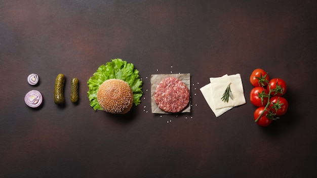 Hamburger ingredients raw cutlet, tomatos, lettuce, bun, cheese, cucumbers and onion