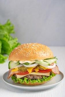 Гамбургер из жареной говядины на гриле, салат, помидор, огурец и бекон на деревянном столе