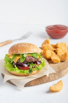 Гамбургер из говядины, сыра, салата, лука и нарезанной булочки, подается с картофельными дольками и кетчупом